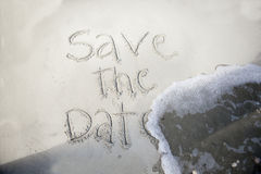 Save the date, in sand. Save the date, written in sand and being washed away by wave Stock Images