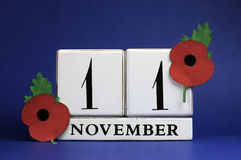 Save the Date, white block calendar, for November 11, Remembrance Day. Red Poppy Day, or Armistice Day holiday, with red Flanders Poppies against a dark blue Royalty Free Stock Images
