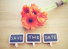 Save the date written on blackboard with flower Royalty Free Stock Photography