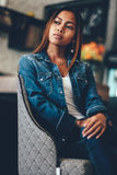Save Download Preview Gorgeous young woman in blue jeans chilling in a club. Portrait of a beautiful young woman Royalty Free Stock Photos