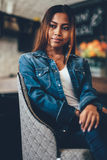 Save Download Preview Gorgeous young woman in blue jeans chilling in a club. Portrait of a beautiful young woman in a club Stock Images