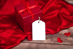Save Download Preview Wrapped red gift box and gift card on the wooden table can use on valentine day mother day or celebrate Royalty Free Stock Photography