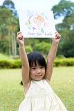 Save the earth. Little kid showing save our earth drawing in a park Stock Photography