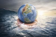 Save the earth concept globe sailing with life buoy in the sea. Save the earth concept globe sailing with life buoy in the blue sea stock photography