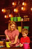 Save Earth concept. Mother and son transplanting flower in new pot to save Earth. Mother and child transplanting. Houseplant in black soil or dirt to save Earth royalty free stock photography