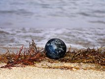 Save the earth and nature. Computer generated Earth-like planet on a beach. Wave crushing in the background stock photography
