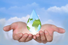 Save Earth/ Water Concept. Hands holding the water drop with world map to suggest save water, save earth, save environment Royalty Free Stock Photo