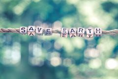 Save Earth word hanging by rope with beautiful green nature boke. H background with vintage retro tone Stock Photo