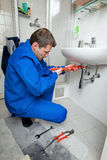 Save energy. Plumber in a bathroom repairs Royalty Free Stock Photography