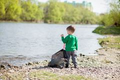 Save environment concept, a little boy collecting garbage and plastic bottles on the beach to dumped into the trash royalty free stock photo
