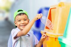A child boy throwing a plastic bottle into a recycle bin