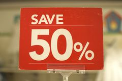 Save fifty percent red sign board. Against a store background Royalty Free Stock Photo