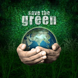 Save the green. Hand holding a globe with green background Royalty Free Stock Photography