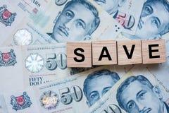 SAVE houten kubus op de achtergrond van het vijftig Dollarsbankbiljet van Singapore zaken, investering, pensionering planning, fi royalty-vrije stock afbeelding