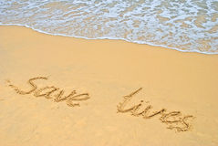 Save Lives. Written on the beach Stock Photo