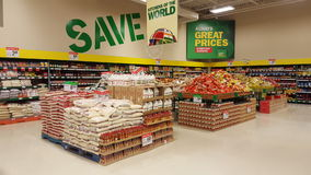 Save money. Discounts in a supermarket groceries. Shelves in a food groceries store. High up on the wall, a billboard with the word save. Another phrase with Royalty Free Stock Photo