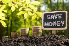 Save Money - Financial opportunity concept. Golden coins in soil Chalkboard on blurred urban background Stock Image