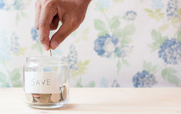 Save money. A male hand putting a coin into the bottle for money saving Stock Images