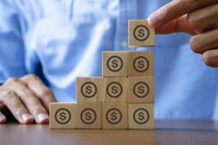 Save money Money management concept.Man hand picking up wooden block with money icon which standing out from other