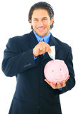 Save Money On Piggy Bank. Young handsome businessman inserting money into piggy bank stock photos
