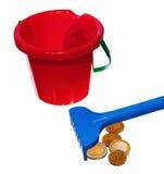 Save money. Raking money with children's rake to red bucket Royalty Free Stock Photo