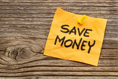Save money reminder note. Save money yellow reminder note against grained wood stock photos