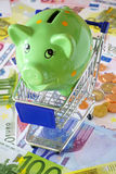 Save money while shopping. Green Piggy Bank in a blue shopping cart on a background made of Euro banknotes and coins Royalty Free Stock Photo