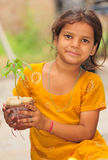 Save nature. Village girl holding green plant Royalty Free Stock Photography