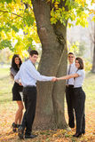 Save The Nature. Group of young business people standing in a park hugging a tree trunk Royalty Free Stock Photography