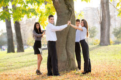 Save Nature. Group of young business people standing in a park hugging a tree trunk Royalty Free Stock Photography