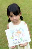Save our earth. Little kid showing save our earth drawing in a park Stock Photos