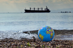 Save our planet. A small color globe of earth on marine beach with a cargo ship on horizon and crushing wave close to the globe are symbols of   ecological Royalty Free Stock Photography