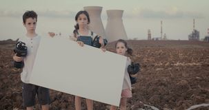 Save our planet. Young kids standing near a refinery with gas masks. Save the planet. young kids holding signs standing with gas mas stock footage