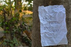 Save paper save trees note hanging on a tree Stock Image