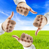 Save the planet. Concept. Four hands showing thumbs up sign over beautiful nature in background Royalty Free Stock Image