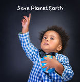 Save Planet Earth. Portrait of cute African schoolboy raised up hand and globe in another hand isolated on blackboard background, text space, save Planet Earth Stock Photography