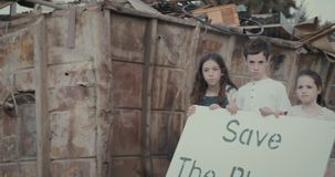 Save the planet. kids holding signs standing in a huge junkyard. Save The planet. young kids holding signs for saving planet earth stock video