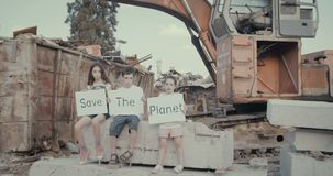 Save the planet. three kids holding signs standing in a huge junkyard. Save The planet. young kids holding signs for saving planet earth stock video
