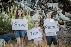 Save the planet. young kids holding signs standing in a huge junkyard Stock Photos
