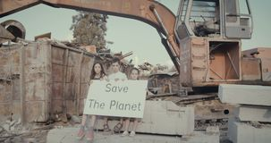 Save the planet. young kids with signs standing in a junkyard. Save The planet. young kids holding signs for saving planet earth stock video footage