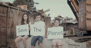 Save the planet. young kids holding signs standing in a big junkyard. Save The planet. young kids holding signs for saving planet earth stock video