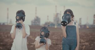 Save our planet - children with gas masks near a big oil refinery. Save the planet. young kids holding signs standing with gas mas stock footage