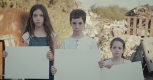Save the planet. young kids holding signs standing in a huge junkyard. Save The planet. young kids holding signs for saving planet earth stock footage