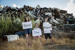 Save the planet. young kids holding signs standing in a huge junkyard Stock Photography