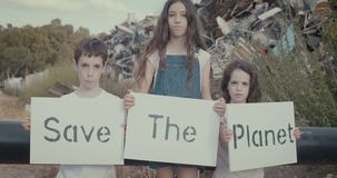 Save the planet. young kids holding signs standing inside a huge junkyard. Save The planet. young kids holding signs for saving planet earth stock video