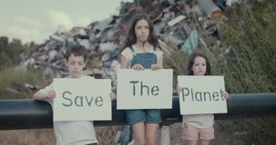 Save the planet. young kids holding signs standing in a large junkyard. Save The planet. young kids holding signs for saving planet earth stock video