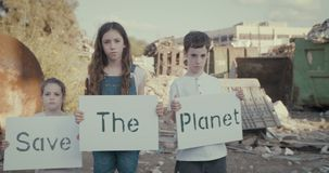 Save the planet. young kids holding signs standing next to huge junkyard. Save The planet. young kids holding signs for saving planet earth stock footage