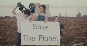 Save the planet. Young kids holding signs near a refinery with gas masks. Save the planet. young kids holding signs standing with gas masks stock video footage