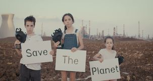 Save the planet. Young kids holding signs standing near a refinery with gas masks. Save the planet. young kids holding signs standing with gas masks stock footage