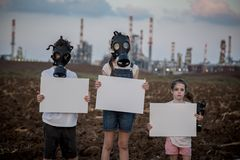 Save the planet. Young kids holding signs standing near a refinery with gas masks Royalty Free Stock Photos